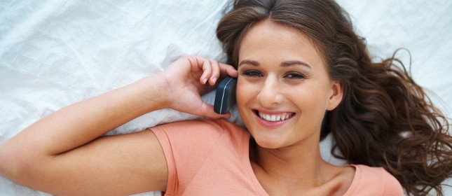 girl phoning on bed